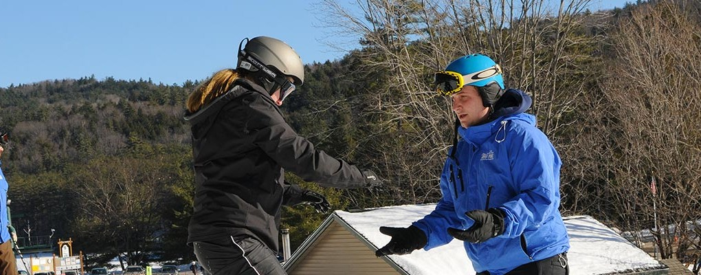 A first-time snowboarder and King Pine snowboard instructor during a lesson at King Pine.