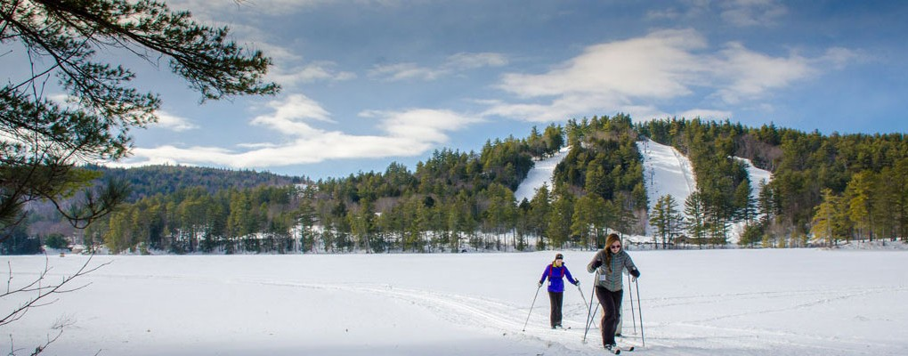Cross country skiers crossing Purity Lake at King Pine Ski Area