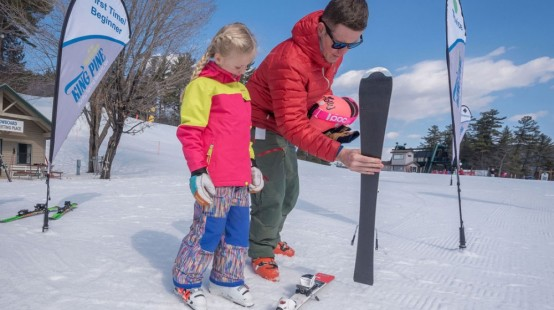 Father and daughter getting ready to ski at King Pine